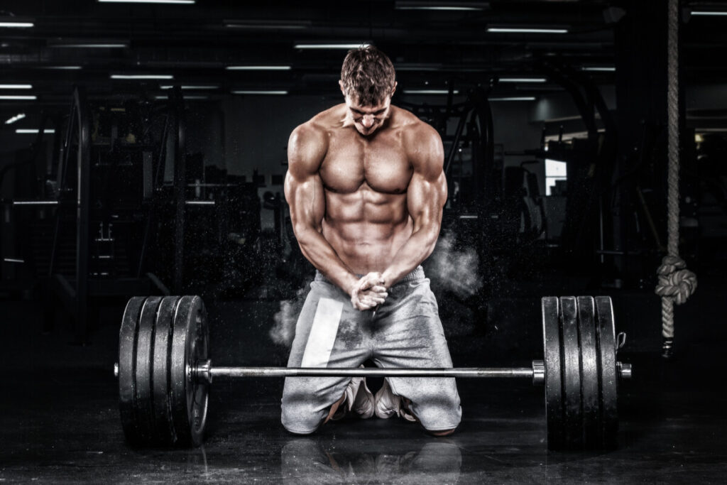 a Athletic shirtless young sports man - fitness model with barbell in gym. bodybuilder doing deadlifts who is using legal steroid t bal 75 to build muscle mass