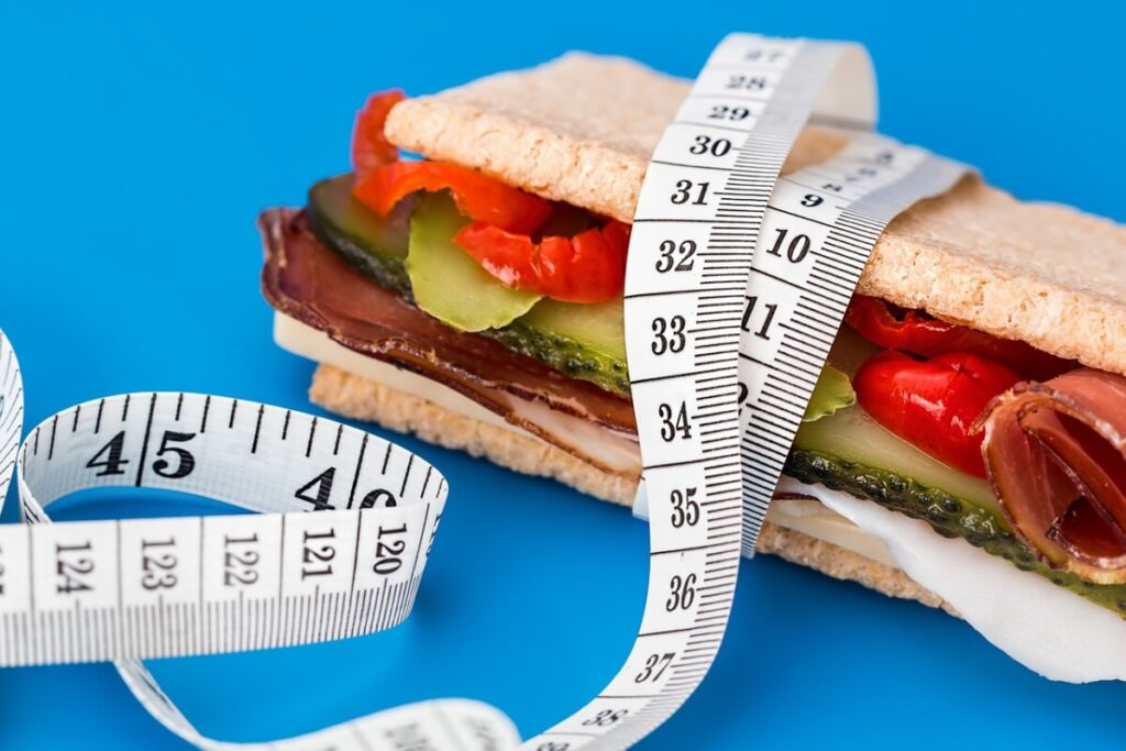 A sandwich with a measuring tape around it referring to the amount of calories you need to eat in order to build muscle