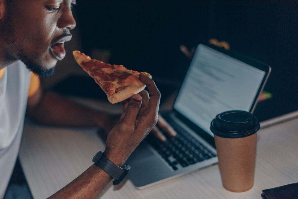 A young black man eating at his desk while working late night. Fitness facts and myth debunked where you can't eat at night