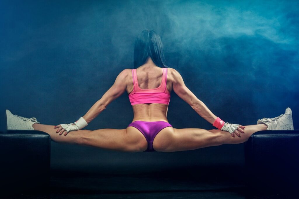 a young woman with muscle defintion doing a split on a balance beam showing her back muscles.