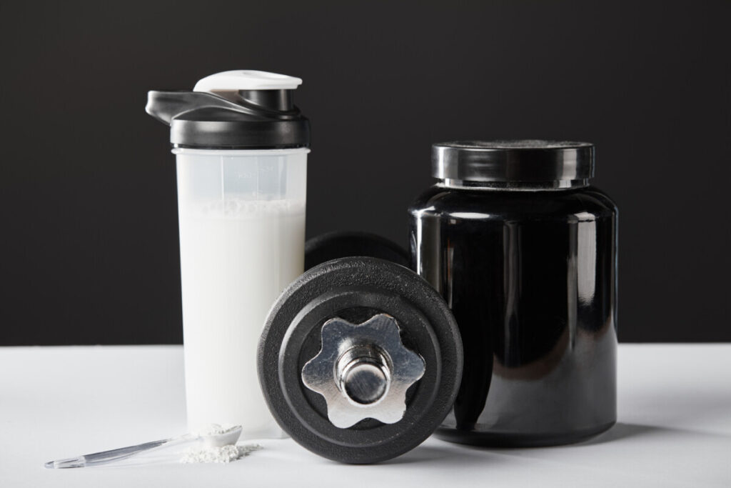 Protein shaker bottle sitting on a table next to a dumbbell