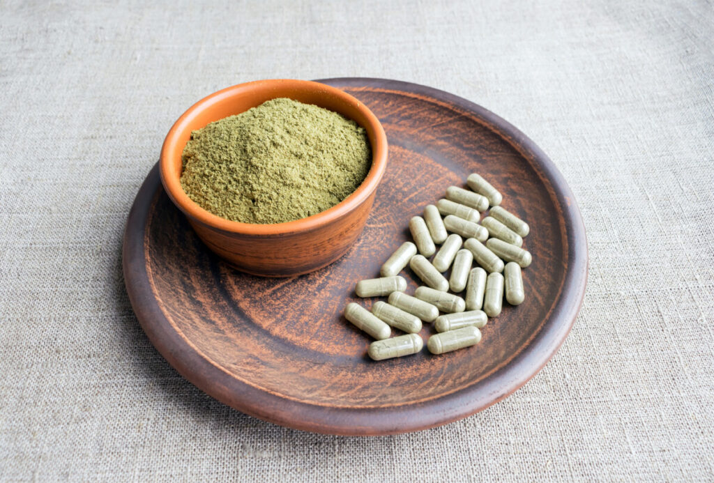 Supplement kratom green capsules and powder on a brown plate. Herbal product alt-medicine kratom is an opioid. Home alternative pain remedy, opioid addiction, dangerous painkiller, overdose. Close up