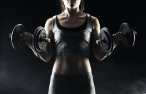 a woman with amuscular tone body doing dumbell curls to increase her strength