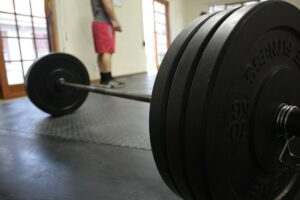 A barbell sitting on the floor loaded with weights resting in between sets