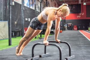 Young woman doing push-ups with parallette bars in gym